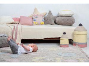 در این تصویر نوزادی را میبینیم که بر روی فرش ماشینی اناق کودک دراز کشیده و بازی میکند.