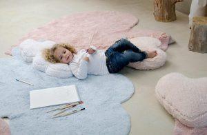 در این تصویر، دختربچهای ذا میبینید که بر روی فرش اتاقش دراز کشیده و مدادرنگیهایش کنارش ریختهاند.