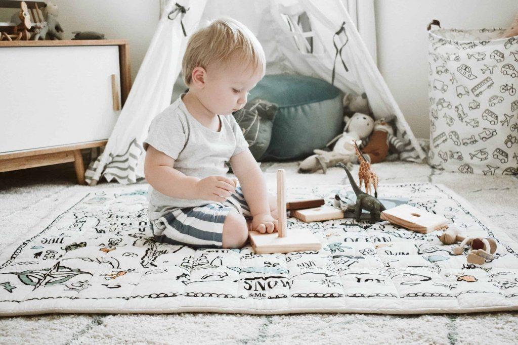 در این تصویر کودکی را میبینید که در اتاق خود و بر روی فرش در حال بازی است.