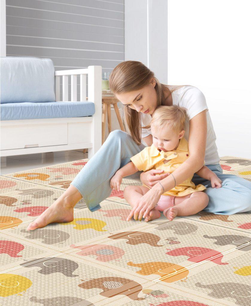 در این تصویر نوزادی را میبینید که در بغل مادرش نشسته و مادرش نقاشی فیلهای کوچک رنگی روی فرش را به او نشان میدهد.